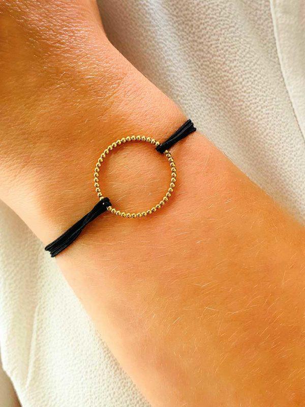 Vue de face gros plan poignet avec bracelet cordon et un cercle en forme de petites boules en plaqué or, et un cordon noir. Bracelet réglable et choix de couleur de cordon
