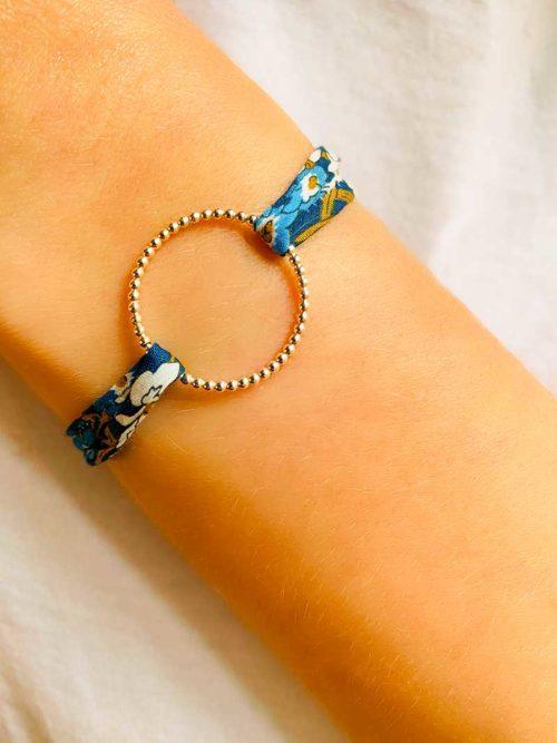 Gros plan vue de face un poignet penché avec un bracelet cordon avec imprimé liberty et un cercle ajouré de petites boules en argent 925