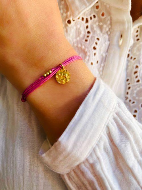 Gros plan poignet avec un bracelet cordon avec une breloque en forme de plaque ronde martelée