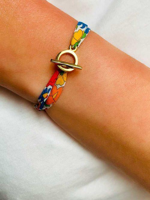 Vue de face gros plan poignet avec bracelet cordon en imprimé liberty et une attache avec une barre dans un cercle en plaqué or