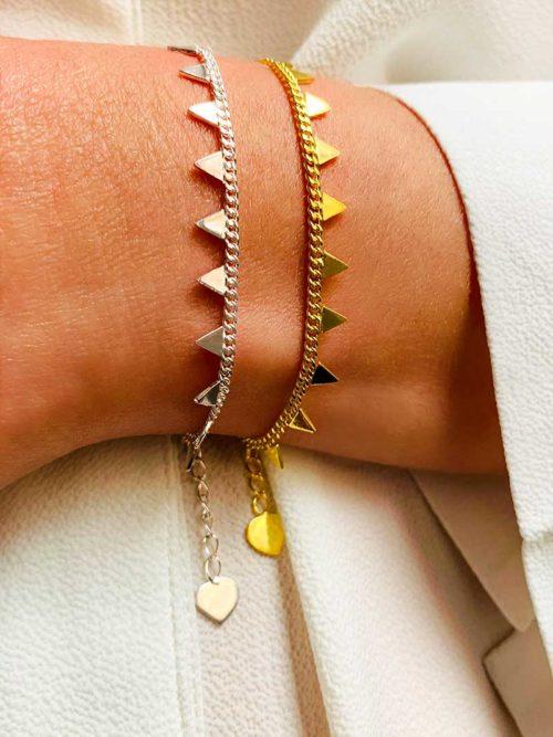 Vue de face gros plan poignet avec deux bracelets identiques l'un en plaqué or et l'autre en argent. Une fine chaîne avec des triangles et attachés par un coeur pendant