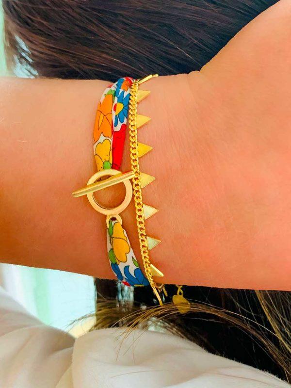 Gros plan poignet relevé contre tête avec deux bracelets en plaqué or, l'un avec un cordon imprimé liberty