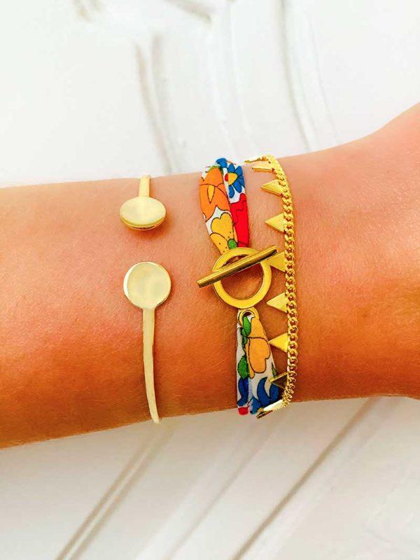 Gros plan poignet avec 3 bracelet en plaqué or. Un jonc ouvert avec plaques rondes. L'un avec un bracelet cordon imprimé liberty. Et le dernier une chaîne avec des pampilles en forme de triangles