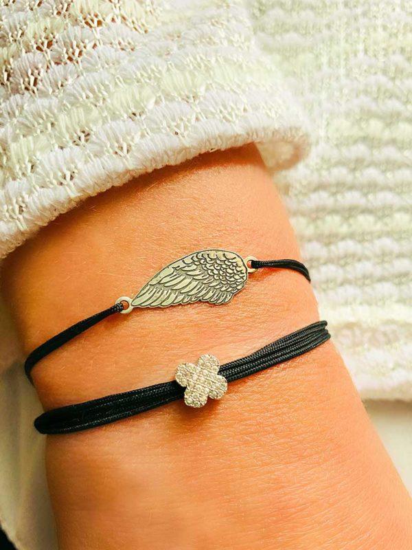 Vue de face gros plan poignet avec deux bracelets cordons avec une aile ciselée en argent et l'autre avec une fleur recouverte de zircons blancs bijoux fantaisies