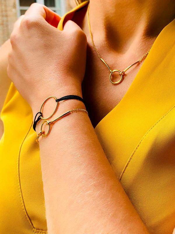 Vue de profil buste avec un bras relevé avec le bracelet Théa et le bracelet cordon Emma doré. Le collier Mya autour du cou. L'ensemble des bijoux sont en plaqué or 925/1000