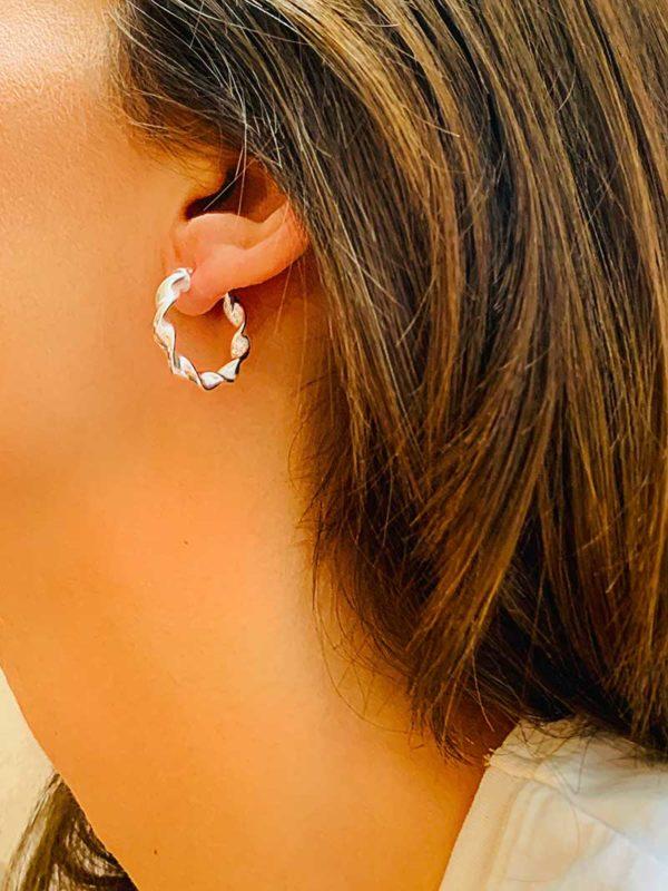 Vue de profil gros plan oreille avec boucles d'oreille style créole en argent avec effet torsadé
