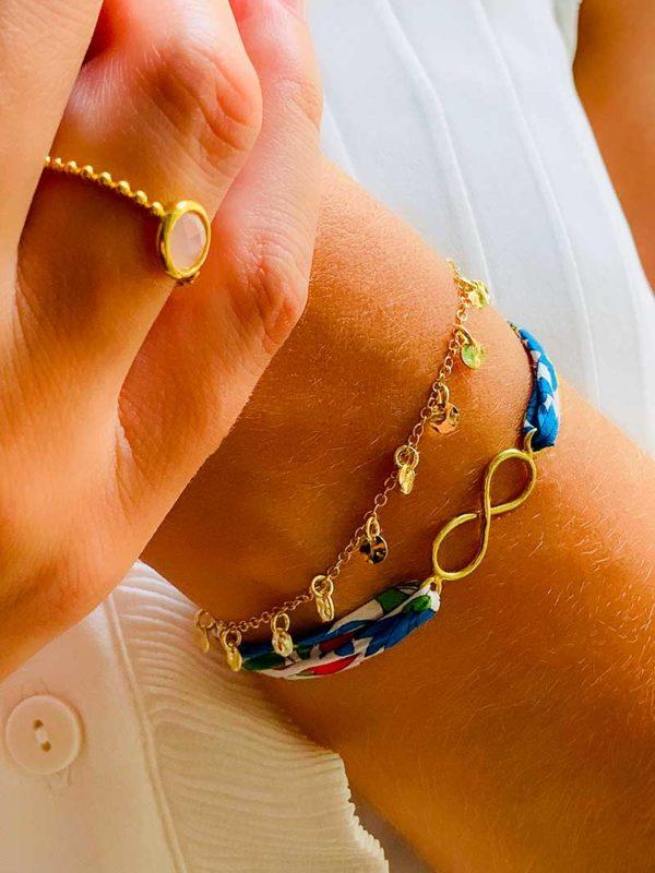 Gros plan main avec une bague en plaqué or et une pierre semi précieuse en quartz rose, et un poignet avec un bracelet chaîne avec des pampilles en forme de petites plaques martelées et un bracelet cordon imprimé liberty et un signe de l'infini en plaqué or. Bijoux fantaisies en plaqué or