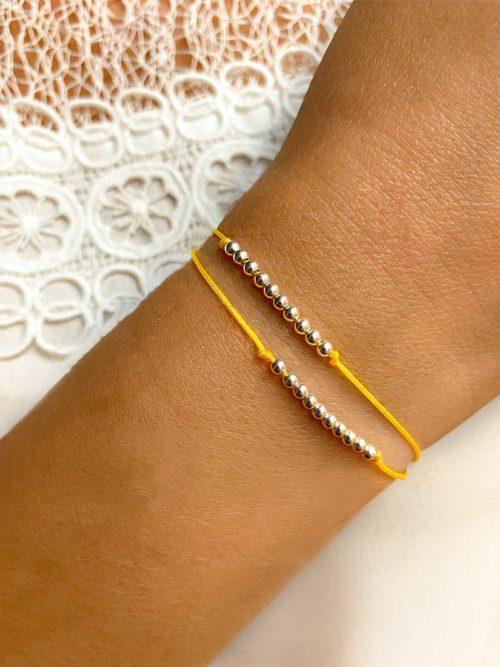 Gros plan poignet avec un bracelet cordon composé de deux rangées de 10 perles chacune. Bijoux fantaisies et personnalisables faits main