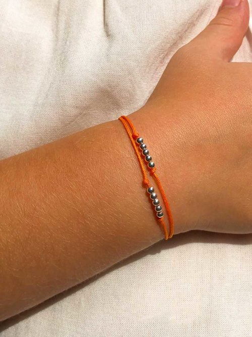 Vue de face gros plan bras enfant avec bracelet cordon avec 2 rangées de 5 petites perles en argent Collection Enfant