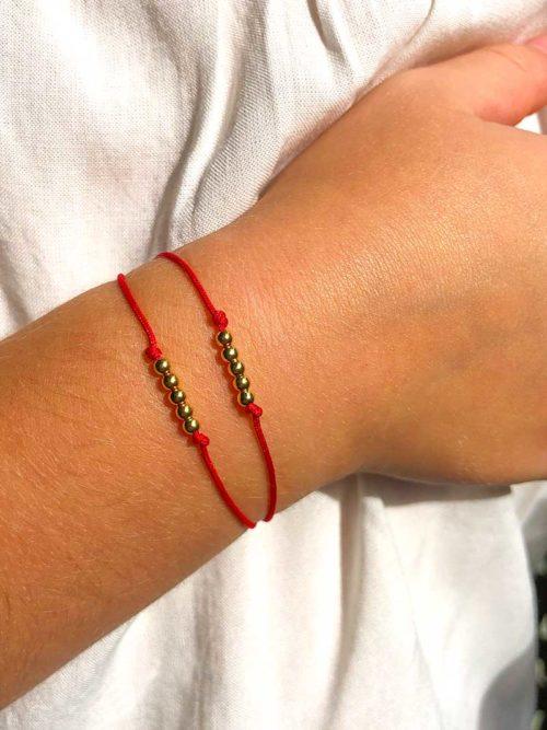 Vue de face gros plan bras enfant avec bracelet cordon avec 2 rangées de 5 petites perles en plaqué or Collection Enfant
