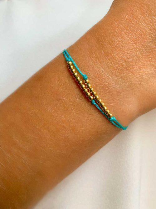 Gros plan poignet avec un bracelet cordon composé de deux rangées de 10 perles en plaqué or chacune. Bijoux fantaisies et personnalisables faits main