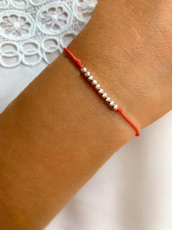 Vue de face gros plan poignet avec bracelet cordon avec 10 perles en argent. Bijoux fantaisie
