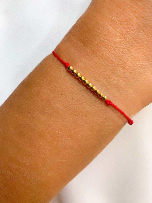 Vue de face gros plan poignet avec bracelet cordon avec 10 perles en plaqué or. Bijoux fantaisie