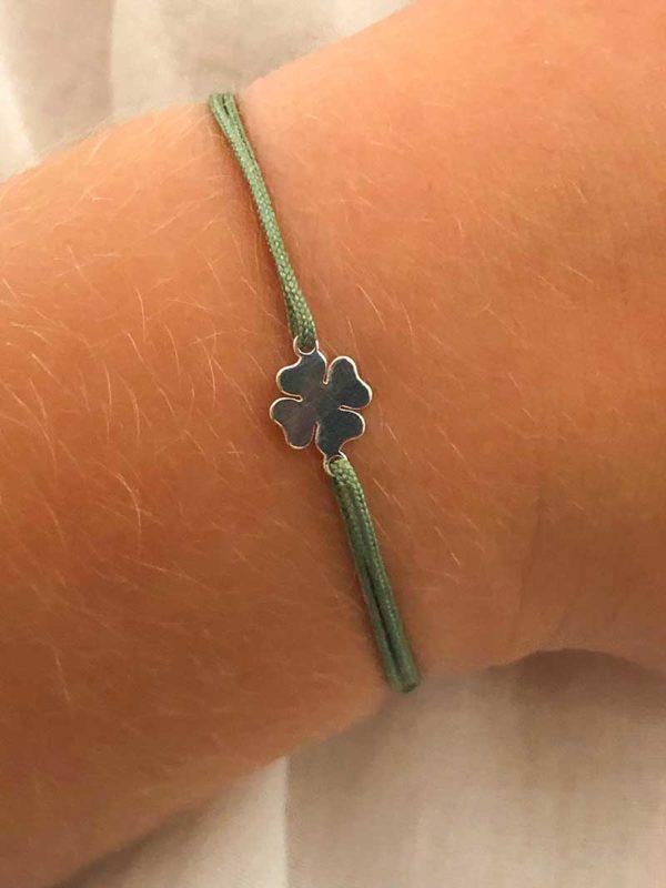 Vue de face gros plan bracelet cordon enfant avec un trèfle en argent