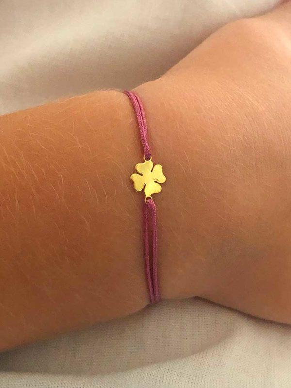 Vue de face gros plan bracelet cordon enfant avec un trèfle en plaqué or