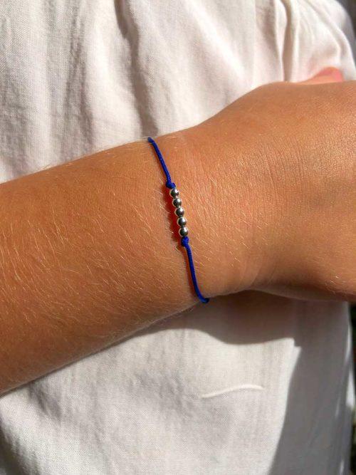 Vue de face gros plan bras enfant avec bracelet cordon avec 5 petites perles en argent Collection Enfant