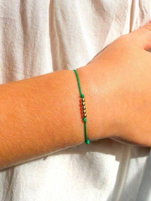 Vue de face gros plan bras enfant avec bracelet cordon avec 5 petites perles en plaqué or Collection Enfant