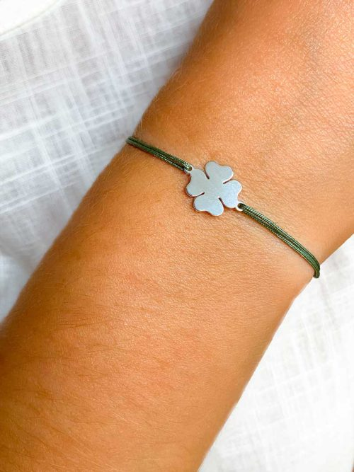 Vue de face gros plan d'un bras avec un bracelet cordon avec un trèfle en argent. Bijoux porte bonheur