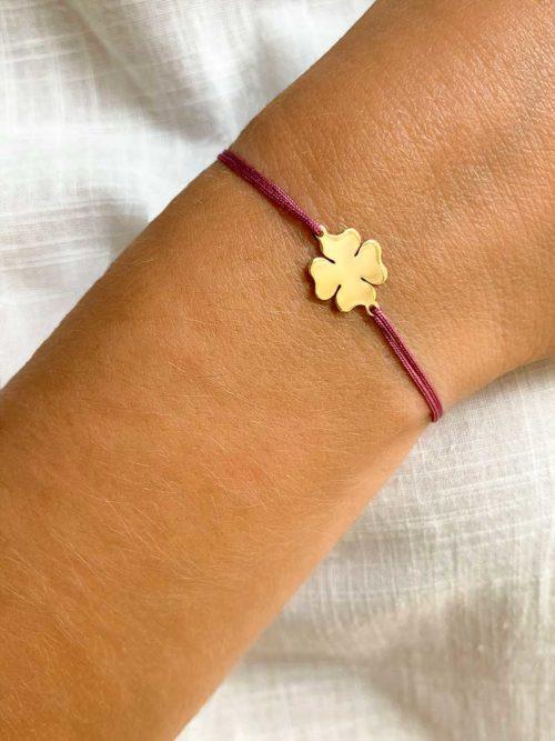 Vue de face gros plan avec un bracelet cordon avec un trèfle à 4 feuilles en plaqué or Bijoux porte bonheur