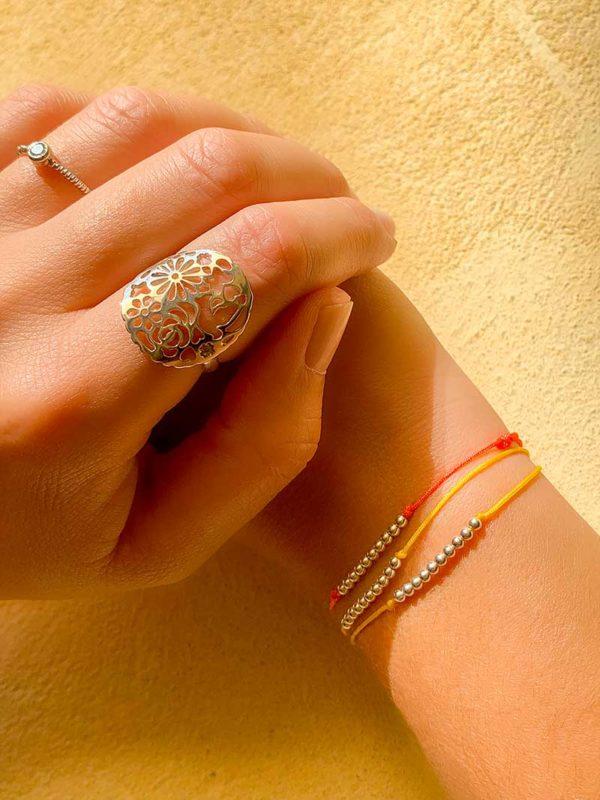 Gors plan mains posées l'une sur l'autre avec au poignet des bracelets cordons avec des petites perles en argent et à l'autre main des bagues en argent et zircons