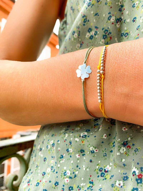 Gros plan bras replié avec deux bracelets cordons au poignet. Un avec une rangée de 10 perles en argent et l'autre avec un trèfle en argent