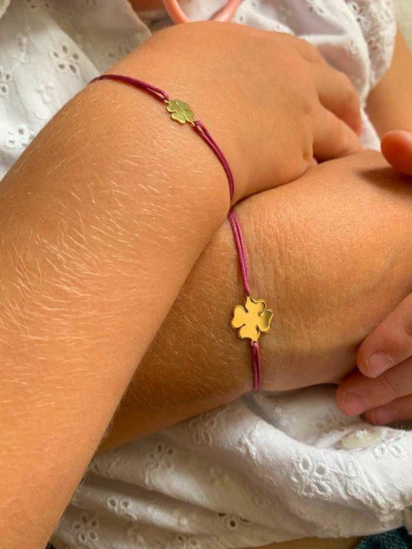 Vue de face gros plan poignetmère et fille avec bracelets cordon identiques avec un trèfle doré