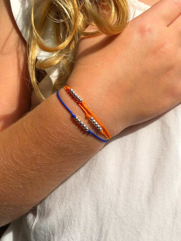 Vue de face petite fille avec au poignet deux bracelets cordons avec des petites perles en argent .
