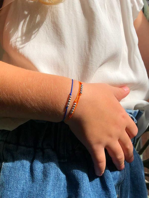 Vue de face main posée sur la taille. Le bras est orné de deux bracelets cordons pour enfant avec des petites perles en argent