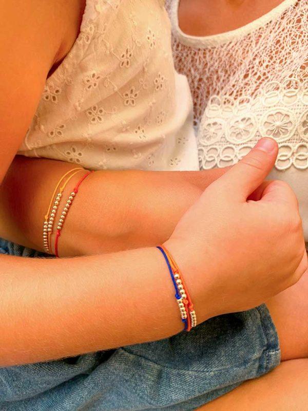 Gros plan bras superposés une mère et sa fille avec des bracelets identiques avec des petites perles en argent Eshop bijoux fantaisies