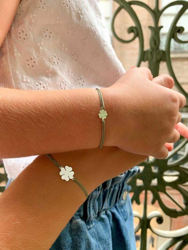 Vue de face gros plan poignets mère et fille avec bracelets cordon identiques avec un trèfle en argent