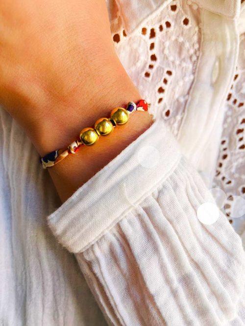 Gros plan poignet femme avec un bracelet cordon imprimé liberty en coton avec 3 perles en plaqué or