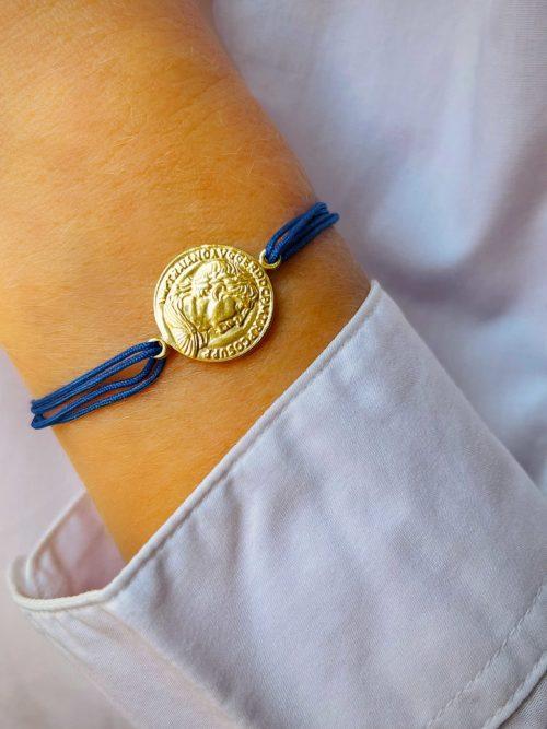 Gros plan poignet avec un bracelet cordon avec une pièce romaine gravée en plaqué or. Bijoux personnalisables