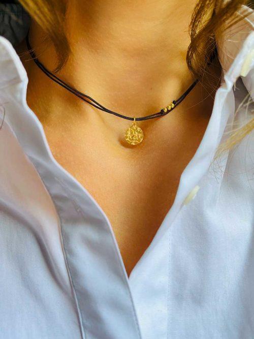 Gros plan cou avec un collier cordon avec une plaque ronde martelée en plaqué or